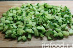 Для салата с консервированным тунцом нарежьте огурцы кубиками. Положите в миску.