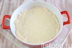 Готовим тесто для сырного пирога с рукколой и базиликом: с помощью скалки растягиваем мучную заготовку в тонкий пласт и выкладываем ее в форму, предварительно смазав жиром.