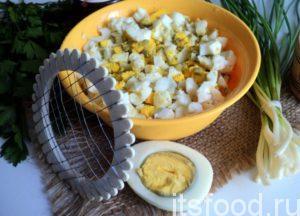 При помощи яйцерезки нарежте яйца.
