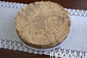 Посыпаем готовый торт оставшимся печеньем, хорошо утрамбовываем массу и отправляем в холодное место. Ждем 12-18 часов.