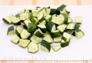 Затем вымойте и нарежте кубиками огурцы. Добавьте к остальным продуктам в салатницу.