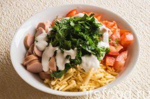 Смешайте сосиски, сыр, помидор и зелень, добавьте сметану. Перемешайте ингредиенты.