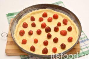 Клубнику моем, удаляем плодоножки. Если ягода крупная, режем на пластинки. Смазываем форму для выпекания маргарином или маслом. Тесто равномерно распределяем по форме, делаем бортик, раскладываем ягоды.