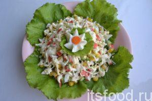 Тщательно смешиваем порезанные ингредиенты. Затем добавляем в ёмкость майонез, а позже выкладываем салатную массу в тарелку на свежие листья зелёного салата. Украшаем готовый салат из крабовых палочек классический яйцом.