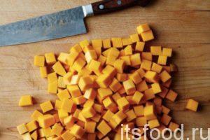 Тыкву очистить от кожуры. Мякоть тыквы нарезать мелкими кубиками. Томаты помыть и порезать так, как тыкву. Подготовленные овощи выложить в бульон к картошке с луком и морковкой.