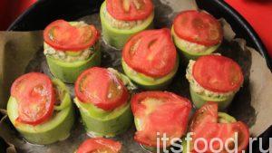 Сверху на фаршированные кабачки укладываем ломтик помидора.