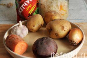 Начинаем готовить борщ с салом и чесноком. Приготовим немного домашней квашеной капусты. Можно сделать такой борщ и со свежей капустой, но квашеная капуста делает борщ вкуснее. Промоем корнеплоды, почистим картофель, морковь и свеклу. Почистим лук и чеснок.