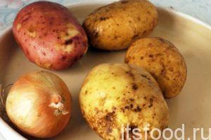 Промоем картофель, поместим в кастрюлю с соленой водой и поставим ее на огонь. Картофель должен свариться в мундирах. Почистим 1 луковицу.