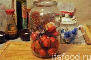 Засыпаем горсть помидоров в заранее подготовленную, ошпаренную кипятком чистую банку, закладываем кусочки чеснока и немного базилика.