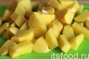 Нарежем очищенный картофель кубиками и отправим его вслед за капустой.