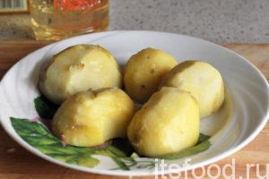 В это время сварился картофель в мундирах. Вынимаем его из воды и удаляем кожицу. Разрезаем картофель на половинки и даем ему немного остыть.