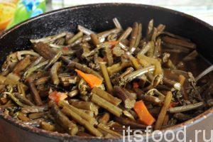Закладываем в сотейник овощную приправу, щепотку кунжута, острые компоненты (перцы) и соевый соус. Высыпаем сверху нарезку папоротника и все перемешиваем. Доводим до закипания.