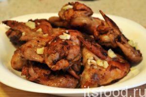 Вынимаем прожаренные куриные крылья из сковороды. Выкладываем их в отдельную посуду и обильно посыпаем мелкой нарезкой свежего чеснока.