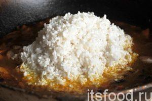 Сливаем с риса воду и осторожно загружаем его в наш казан. Загружаем по центру, а затем аккуратно сдвигаем распаренный рис к краям.