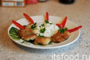 Минтай с рисом готов. Выкладываем отваренный рис и кусочки жареной рыбы на плоские тарелки. Украшаем блюдо листочками петрушки и нарезкой сладкого перца.