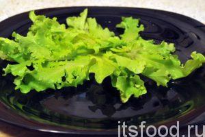 Начинаем сервировку блюда. На большие плоские тарелки выкладываем свежие листья салата.