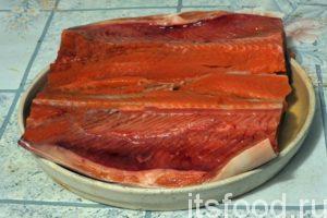 Вернемся к тушке нашего лосося. Ее, для вкусного посола по-домашнему, необходимо распластать вдоль хребта, не прорезая кожу рыбы. Производим разрез. Рыба поделена на две половинке, одна из них содержит хребтовую кость. Поместим рыбу в неглубокую емкость, где мы будем солить лосося по-домашнему.