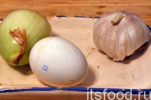 Приготовим лук, чеснок и куриное яйцо. Лук и чеснок нужно очистить от кожуры. Лук нарезается на четвертинки для облегчения его размола в стакане погружного блендера. Чеснок также нарезаем на пластинки.