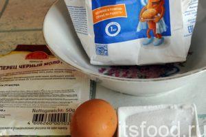 Возьмем нужное количество муки и поместим ее в глубокую чашку, туда же разобьем одно сырое яйцо, добавим соль, молотый перец и немного воды.