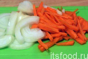 Нарежем лук полукольцами, а морковь можно нарезать брусочками. Из казана, где уже вытопился бараний жир, убираем шкварки и загружаем нарезку моркови и лука.
