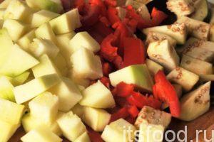 Нарежем на небольшие кубики кабачок и баклажан. Красный сладкий перец нарежем соломкой. Отправляем нашу нарезку вслед за луком. Все овощи нужно перемешать и добавить половину стакана воды, соль и сахар.