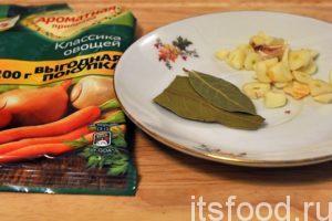 Добавляем в сковородку с мясом и подливом овощную приправу, лавровый лист, соль и нарезку чеснока.
