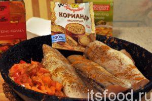Сдвигаем овощи, добавляем немного растительного масла и закладываем порционные куски рыбы, которые обжариваем с двух сторон по 3 минуты. Добавляем пряности.