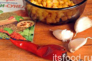 Приготовим один острый маринованный красный перец чили (можно взять свежий перчик), несколько столовых ложек консервированной кукурузы, приправу хмели-сунели и три зубчика чеснока. Острый перец нарежем колечками. Чеснок порежем на тонкие пластики. Все компоненты добавляем в сковородку.