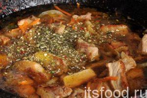 Добавляем в сковороду со свининой и овощами сухую растительную приправу. Продолжаем тушить свинину на слабом огне.