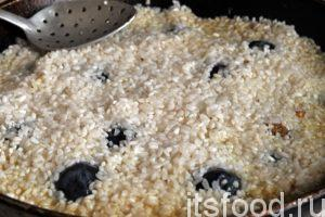 Сливаем из емкости с рисом остывшую воду и промываем его еще раз. Рис увеличился в размерах и набух. Аккуратно выкладываем его поверх зирвака с чесноком и сливами. Выравниваем поверхность.