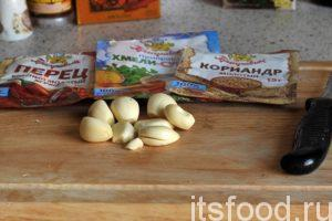Постоянно помешивая овощное рагу с баклажанами, начинаем замечать, что постепенно растворились кусочки тыквы и кабачков. Специальной стальной толкушкой с отверстиями пробуем сделать рагу более однородным. Добавляем в жаровню приправы и нарезку чеснока. Продолжаем тушить еще 2-3 минуты.