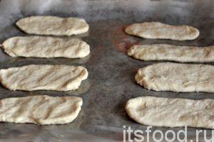 С помощью скалки, или руками, смазанными подсолнечным маслом формируем из наших колбасок плоские язычки. Готовые полуфабрикаты выкладываем на лист специальной бумаги для выпечки, которая заранее смазана растительным маслом и помещена на противень. После того, как я купил рулончик такой бумаги, я забыл, что такое мытье противня. Язычки готовы к выпечке в духовом шкафу. Его не нужно предварительно нагревать. Это поможет язычкам подняться.