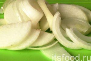 Нарежем лук полукольцами и загрузим его вслед за морковью.