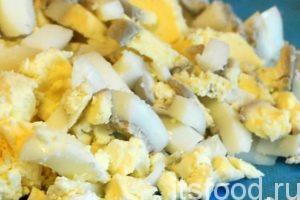 Нарежем куриное яйцо, сваренное вкрутую, и добавим его в кастрюлю. Все перемешаем. У нас в кастрюле обязательно должно остаться немного подливы.