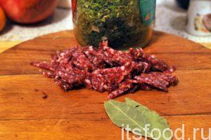 Нарежем соломкой сырокопченую колбасу и добавим ее в солянку. Добавляем лавровый лист и сушеную зелень. Пробуем блюдо на соль и добавляем ее, если это нужно.