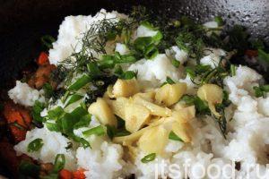 Накладываем рис в сковородку поверх мяса и овощей, добавляем обжаренные ранее дольки чеснока и немного нарубленной зелени.