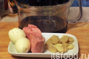 Мы будем использовать очень простой кухонный комбайн, который поможет нам нарезать все компоненты на ровные кубики. Приготовим (очистим от скорлупы) отваренные куриные яйца, нарежем колбасу на крупные кусочки. Начинаем забрасывать наши продукты в комбайн. Он легко выполняет свою задачу.