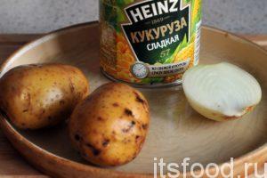 Промоем пару картофелин и приготовим половинку репчатого лука. Откроем баночку консервированной кукурузы.