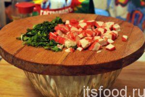 Теперь содержимое приемного бункера можно переместить в большой глубокий салатник, где и будет происходить приготовление салата. Крабовые палочки извлечем из упаковок и мелко нарежем на доске обычным ножом. Нарежем зелень петрушки и добавим нашу нарезку в салатник.