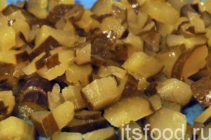 Нарежем соленые огурцы на мелкие кубики и добавим их на сковородку с овощами. Все перемешиваем и продолжаем тушить еще 5-7 минут.