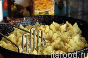 Специальной толкушкой слегка разминаем наш картофель и перемешиваем его с содержимым сковородки. Можно добавить немного соли и черный молотый перец (по желанию).