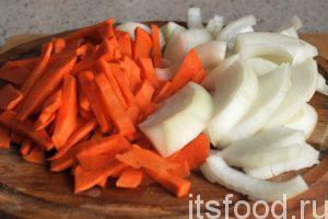 Нарежем морковь на крупные брусочки, а лук на полукольца и поместим нашу нарезку в казан, где обжаривается мясо гуся. Все перемешаем и продолжаем обжаривать зирвак для плова на среднем огне.