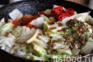 Закладываем поверх мяса с луком нарезанную капусту, добавляем соевый соус, сухую овощную приправу, парику молотую и нарезку малосольного перца чили. Добавляем 1 стакан кипятка, все перемешиваем и начинаем тушить до готовности капусты. На это уйдет еще полчаса.