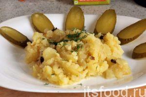 Раскладываем по плоским тарелкам нашу толченку с луком и добавляем дольки соленого огурца.