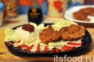 Филе курицы в кляре на сковороде готово. Подаем на стол на больших плоских тарелках покрытых листьями салата. На гарнир отлично подойдет отваренный рис. Томатный соус и кусочки красного сладкого перца будут к месту.