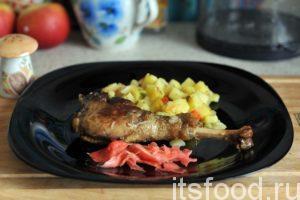 Тушеный гусь с картошкой готов. Выкладываем на плоские тарелки гусиные ножки и добавляем сочный картофель. Украшаем блюдо маринованным имбирем.