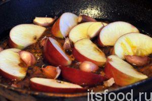 За это время наш кипяток почти весь выкипит, а зирвак станет концентрированным бульоном, который готов принять рис. Режем наше яблоко на дольки и выкладываем их равномерно по всей поверхности зирвака. Чеснок разбираем на зубчики, и тоже выкладываем его в казан.