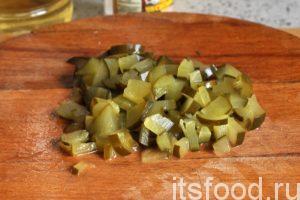 Нарежем соленый огурец на небольшие дольки и добавим его в салатник.