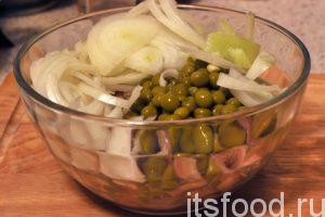 В большой салатник выкладываем кусочки сельди, нарезку репчатого лука и зеленый горошек без сока.