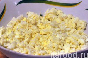 Почистим остывшие яйца и мелко покрошим их. Соединим яйца с нарезкой зеленого лука и перемешаем начинку. Добавим соль, если это нужно.